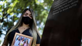 "Thamires da Silva Netto, 29, who lost five relatives to the coronavirus disease (COVID-19), participates in a ceremony at the ""Infinity Memorial"" for the victims of the covid-19, where the name of her mother and sister were written, at the Penance Cemetery in Rio de Janeiro, Brazil, 08 January 2021"