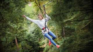 A woman in a Go Ape harness