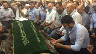 Mourners with the coffin of Sheikh Afiyuni