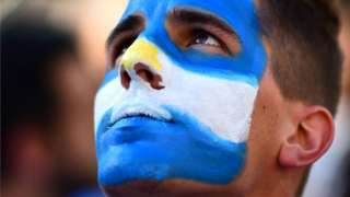 Macri supporter with face painted like Argentine flag