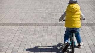 Niño de espaldas en bicicleta.
