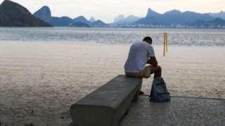 Homem olhando para baixo e sentado em banco na beira de praia em Niterói, com vista do Rio de Janeiro ao fundo