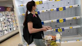 A woman shopping in a supermarket walks past empty shelves