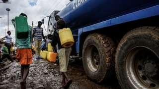 Des enfants kényans transportant des bidons à la recherche d'eau.