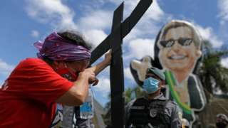 A demonstrator holds a cross at a protest against Bolsonaro and his handling of the pandemic