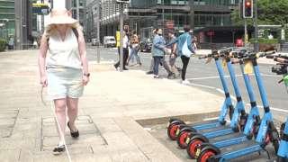 Karishma Shah walking past e-scooters