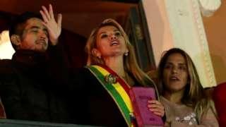 Jeanine Áñez holding a bible as she addresses supporters from a balcony.