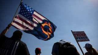 A supporter of President Donald Trump holds an US flag with a reference to QAnon
