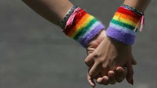Two people holding hands wearing rainbow wristbands