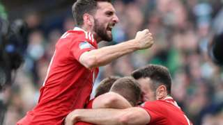 Graeme Shinnie celebrates with his team-mates after Jonny Hayes' late winner