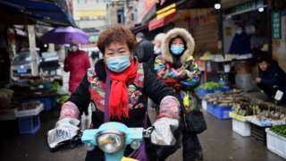 A woman wearing a face mask to help stop the spread of a deadly virus which began in the city rides her scooter through a market in Wuhan, 24 January 2020