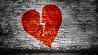 Corazón partido pintado en una pared.
