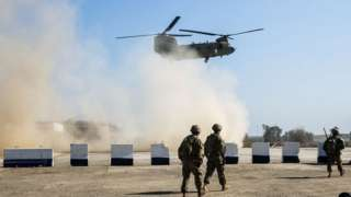 US troops walk as a US Army C-47 Chinook helicopter flies over the village of Oreij, south of Mosul, on February 22, 2017