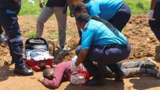 Paramedics tend to a person who was injured by police during protests in Mbabane on October 20, 2021.