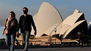 People wearing masks walk past the Sydney Opera House during a state-wide lockdown in August 2021