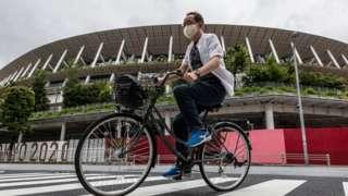 A man rides bicycle past Olympics Stadium