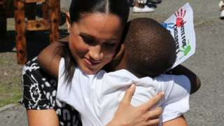 Meghan shares a hug with a youngster