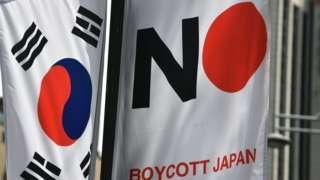 A South Korean flag and a banner that reads Boycott Japan