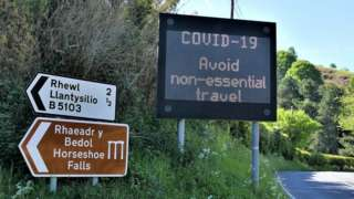 A road sign telling people to avoid essential travel