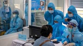 Nhân viên y tế Việt Nam thu thập thông tin từ một người được tiêm vaccine AstraZeneca COVID-19 hôm 8/3/2021