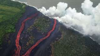 Steam plumes rise as lava enters the Pacific Ocean, after flowing to the water from a Kilauea volcano fissure, on Hawaii's Big Island on May 21, 2018 near Pahoa, Hawaii.