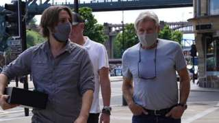 Harrison Ford, wearing a face mask, on Newcastle Quayside with the Tyne Bridge in the background