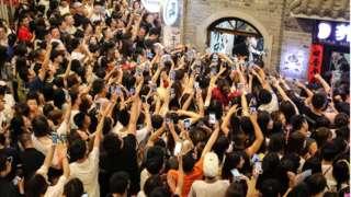Fãs gravam vídeos em seus smartphones enquanto a boyband Modern Brothers se apresenta durante um webcast ao vivo na Andong Old Street em 30 de junho de 2018 em Dandong, província de Liaoning na China.