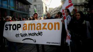 """Activists hold a banner that reads: """"Stop Amazon and its world"""" as they demonstrate in Nantes, France, November 29, 2019"""