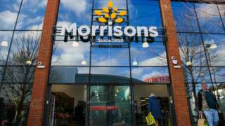 Shoppers are seen with Morrison shopping bags outside a branch of Morrison supermarket