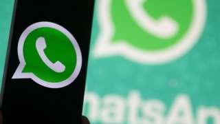 Logo de WhatsApp en un teléfono con pantalla oscura