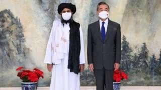 中國外交部長王毅(右)和阿富汗塔利班政治委員會負責人巴拉達爾(Mullah Abdul Ghani Baradar)