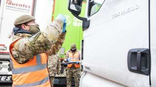 British Army soldier delivering a Covid-19 test to a lorry driver at Manston airfield in Kent on 25 December