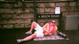 A man lying on a blanket in front of a street sign