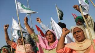 Women shout slogans at an expressway which was blocked by farmers to mark the 100th day of the protest against the farm laws, near Kundli border, in Haryana, India, March 6, 2021