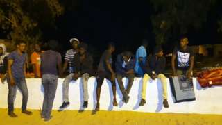 People gather outside the Tajoura Detention Centre after an air strike kills nearly 40 migrants east of Tripoli, 3 July