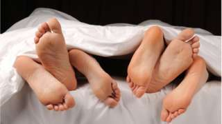 Legs of at least three pipo wey dey ontop bed