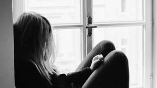 Generic image of teenage girl looking out of window