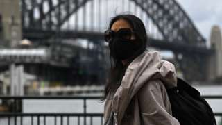 A woman walks past the Sydney Harbour Bridge after stay-at-home orders were lifted across NSW, in Sydney, Australia, Tuesday, October 12, 2021