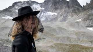 """A woman takes part in a ceremony to mark the """"death"""" of the Pizol glacier"""