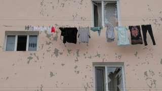 Laundry hanging on a building next to shattered windows in Stepanakert, after shelling