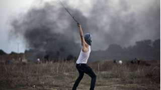 A Palestinian protester uses a slingshot to throw stones towards Israeli soldiers during clashes near the border fence between Israel and the central Gaza Strip east of Bureij on 15 October 2015.