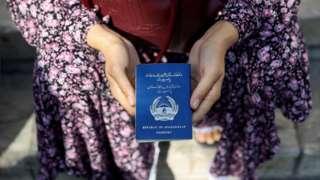 Afghan refugee holding her passport