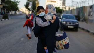A Palestinian woman carries her son after their apartment building was hit in an Israeli air strike in Gaza City (12 May 2021)