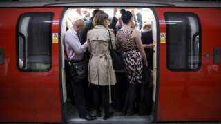 Commuters squeeze into a crowded Tube carriage