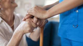 Care home worker holding a resident's hands