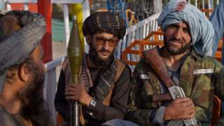 Taliban fighters pose with weapons at a fairground on 28 September, 2021
