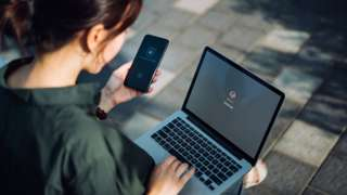 File image of woman with phone and laptop