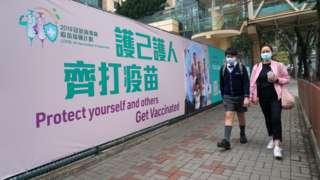 路人走过铜锣湾香港中央图书馆社区疫苗接种中心外的大型宣传横幅(5/3/2021)