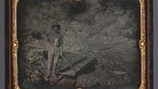 Foto mostra um homem negro não identificado trabalhando em uma mina de ouro em 1852