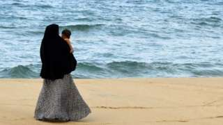 In this picture taken on April 25, 2019, a Sri Lankan Muslim woman walks along a beach with her child in Kattankudy. - Zahran Hashim's sword-wielding zealotry fuelled fears in the sleepy east coast town of Kattankudy long before the cleric became Sri Lanka's most wanted man over the horrific Easter Sunday suicide attacks. The country's president announced on April 26 that Hashim led and died in the attack on the Shangri-La hotel in Colombo -- one of three hotels and three churches hit by bombers wearing explosive backpacks.